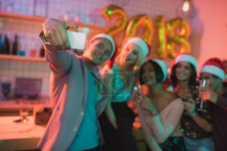 Photo for Selective focus of multiethnic friends taking selfie together on smartphone during new year party - Royalty Free Image