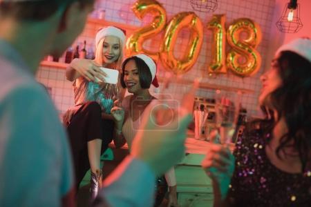 Foto de Sonriente a mujer multicultural teniendo selfie durante fiesta de año nuevo con amigos - Imagen libre de derechos