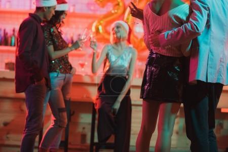 Photo pour Mise au point sélective des amis multiethniques fête de nouvel an en bar - image libre de droit