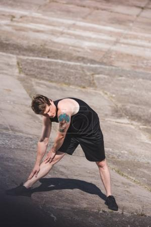 Photo for Young man in sportswear stretching on slabs alone - Royalty Free Image