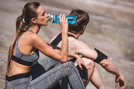 Photo for Side view of woman drinking water from sportive bottle while man resting near by - Royalty Free Image