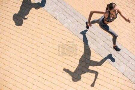 Photo for Overhead view of young woman in sportswear jogging on street - Royalty Free Image