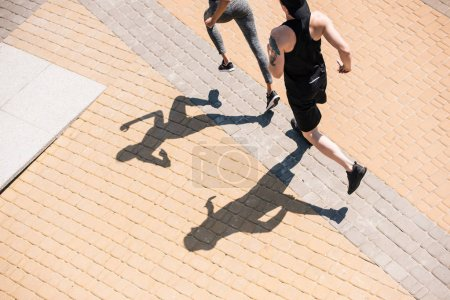 Photo for Overhead view of sportive couple jogging on street together - Royalty Free Image