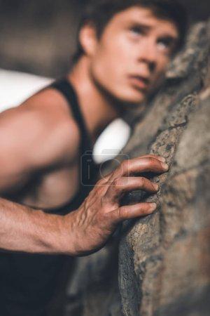 sportive man climbing on ruins