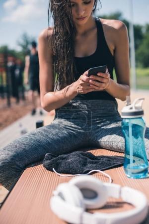 Photo pour Portrait de femme sportive à l'aide de smartphone tout en se reposant après une formation sur banc - image libre de droit