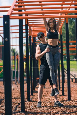 trainer helping woman