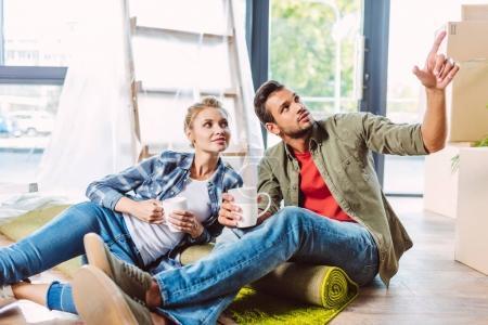 Paar trinkt Tee in neuer Wohnung