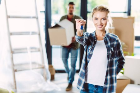 Photo for Smiling young woman holding keys while boyfriend standing behind in new house - Royalty Free Image