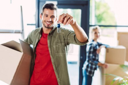 Photo for Smiling young man holding keys while girlfriend standing behind in new house - Royalty Free Image