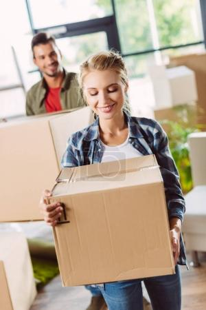 Photo for Happy young couple carrying cardboard boxes in new apartment - Royalty Free Image