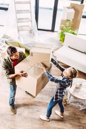 Photo for High angle view of happy young couple holding cardboard boxes in new house - Royalty Free Image