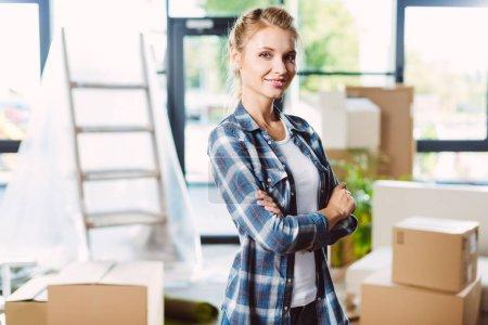 Photo pour Attrayant jeune femme debout avec les bras croisés et souriant à la caméra dans une nouvelle maison - image libre de droit