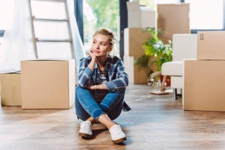 Photo for Pensive young woman looking away while sitting on floor in new house - Royalty Free Image