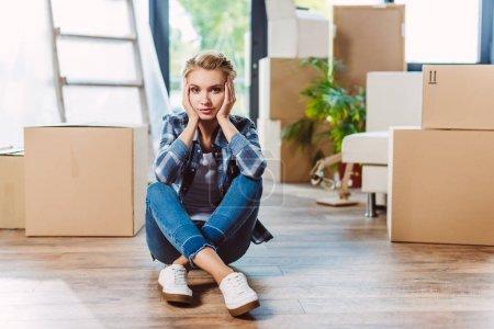 Foto de Grave joven mirando a cámara mientras está sentado en el piso en la casa nueva - Imagen libre de derechos