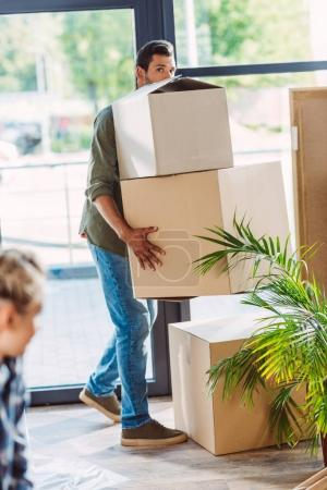 Photo for Young man holding cardboard boxes and looking at camera while relocating in new house - Royalty Free Image