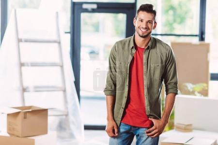 Photo pour Beau jeune homme souriant à la caméra tout en se tenant dans une nouvelle maison - image libre de droit