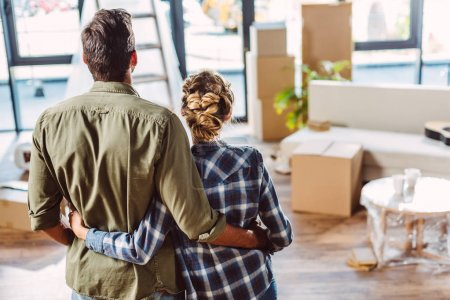 Photo for Back view of young couple embracing in new house - Royalty Free Image