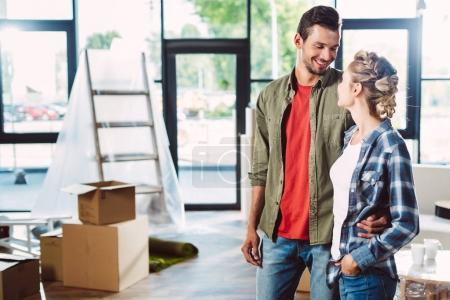 Photo pour Heureux jeune couple souriant mutuellement en position debout ensemble dans Maison Neuve - image libre de droit