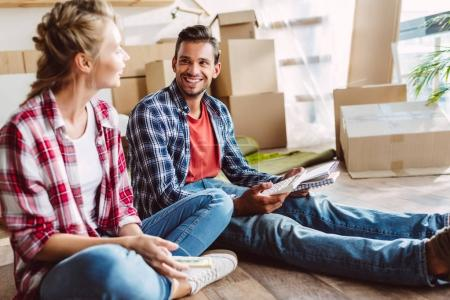 Photo for Smiling young couple counting money while sitting on floor in new apartment - Royalty Free Image