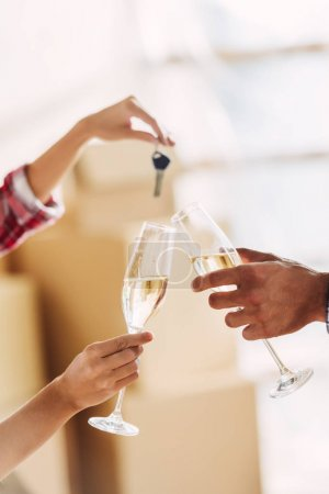 Photo for Cropped shot of couple holding glasses of champagne and keys from new house - Royalty Free Image