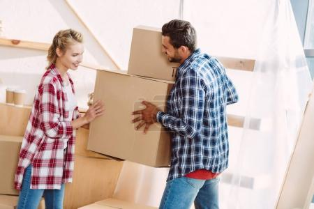 Photo for Happy young couple holding cardboard boxes while moving in new house - Royalty Free Image