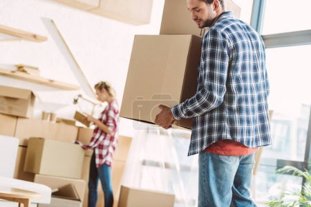 Photo for Handsome young man holding cardboard boxes while girlfriend standing behind in new house - Royalty Free Image