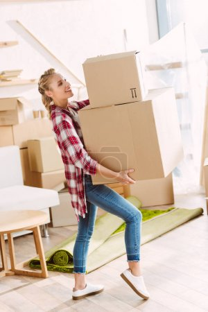 Photo for Beautiful smiling young woman holding cardboard boxes while moving in new house - Royalty Free Image