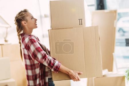 Photo pour Vue latérale d'une jolie jeune femme tenant des boîtes en carton à l'intérieur - image libre de droit
