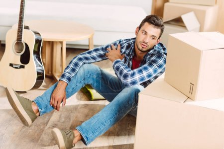 Photo for Pensive young man looking at cardboard boxes while sitting on floor in new house - Royalty Free Image