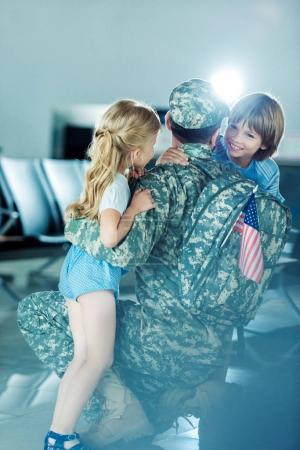 Photo pour Enfants heureux hugging père en uniforme militaire à l'aéroport - image libre de droit