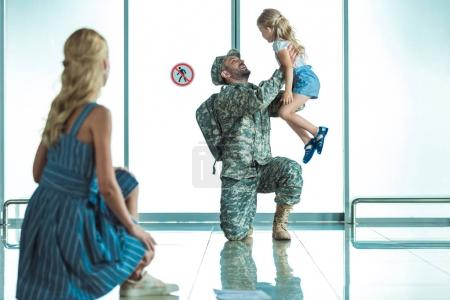 mother and daughter meeting father in airport
