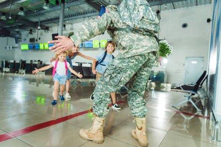 Photo pour Père de Happy réunion familiale en uniforme militaire à l'aéroport - image libre de droit