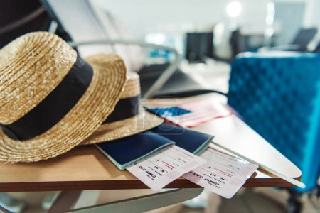 Photo for Close up view of hats, passports with tickets and american flag on wooden chair at airport - Royalty Free Image