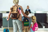 family going to check in desk