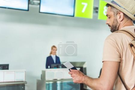 Photo pour Vue latérale de l'homme tenant le passeport et le billet en main en attendant au comptoir d'enregistrement à l'aéroport - image libre de droit
