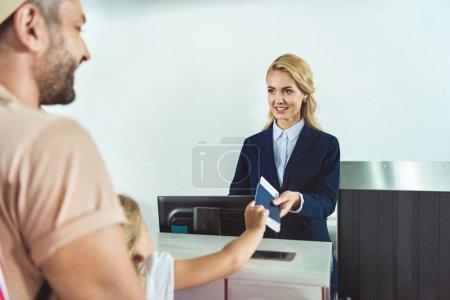 Photo pour Vue partielle de l'enfant donnant passeport et billet au personnel au comptoir d'enregistrement à l'aéroport - image libre de droit