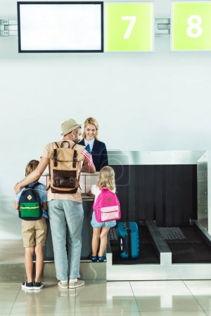 family at check in desk at airport