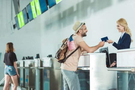 Photo for Side view of smiling man giving passport to staff at check in desk at airport - Royalty Free Image