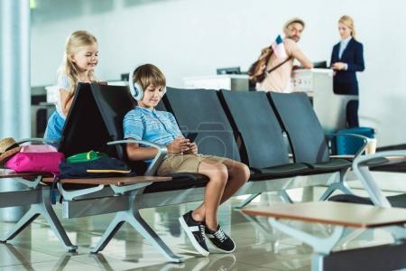 Photo pour Garçon dans les écouteurs en utilisant smartphone avec soeur à proximité et père à l'enregistrement au bureau à l'aéroport - image libre de droit