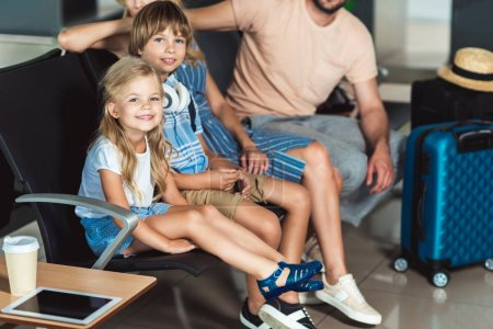 Photo for Young family waiting on seats for boarding at airport - Royalty Free Image