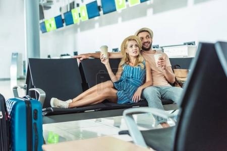 Photo for Couple with coffee to go resting on seats while waiting for boarding at airport - Royalty Free Image
