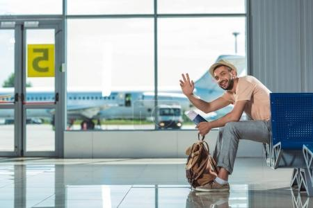 man waving to someone in airport