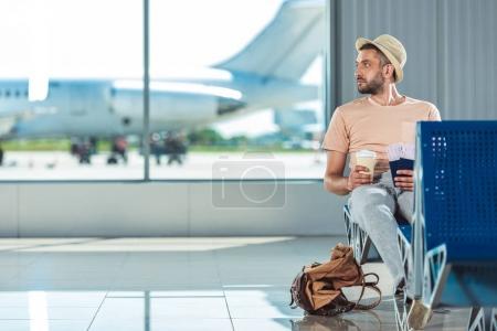 Photo pour Voyageur avec passeports et billets en attente pour quelqu'un à l'aéroport - image libre de droit