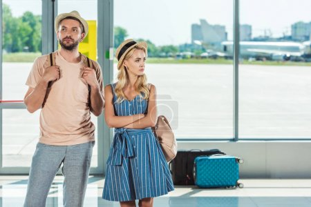 Photo for Portrait of couple looking away while waiting for boarding in airport - Royalty Free Image