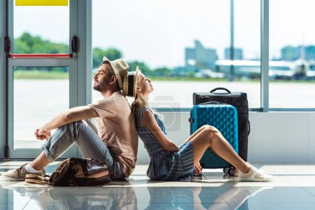 Photo for Side view of couple sitting back to back while waiting for boarding in airport - Royalty Free Image