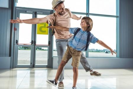 Photo for Father and little son having fun together while waiting for boarding in airport - Royalty Free Image