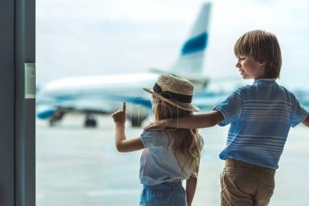kids looking out window in airport