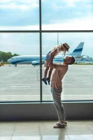 Photo for Father and little daughter having fun together while waiting for boarding in airport - Royalty Free Image