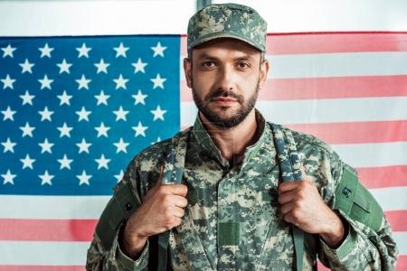 Photo pour Portrait de soldat en uniforme militaire regardant de caméra contre drapeau américain - image libre de droit