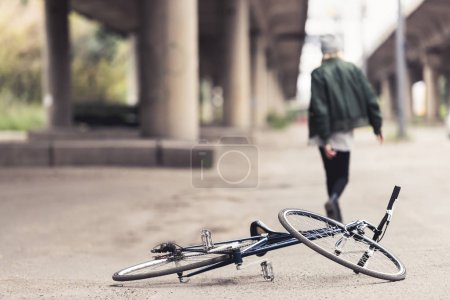 Photo for Woman walking away from vintage bicycle laying on asphalt - Royalty Free Image